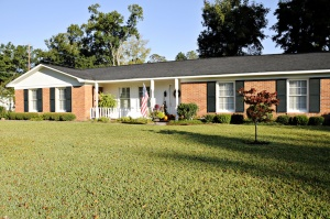 Lovely Ranch style home of red brick, white trim and black shutters with an American Flag.